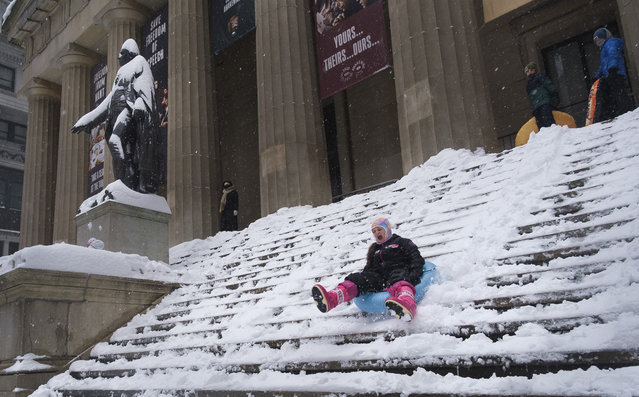 Children sled down the steps of Federal Hall, at left is a snow covered statue of George Washington, as snow falls in New York, New York, USA, 01 February 2021. According to reports, about 15 cm (six inches) of snow has already fallen in the city and total snow accumulation is expect to be up to 50 cm (about 20 inches) by Tuesday 02 February. The large storm is causing hazardous travel conditions and flight cancellations up and down the East Coast of the United States. (Photo by Justin Lane/EPA/EFE)