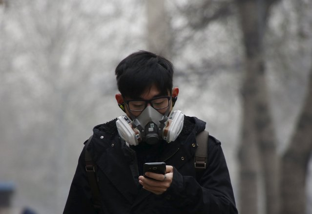 "A man wearing a mask uses his mobile phone amid heavy smog after the city issued its first ever ""red alert"" for air pollution, in Beijing, China, December 8, 2015. (Photo by Kim Kyung-Hoon/Reuters)"