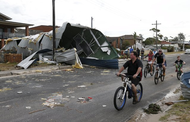 Residents from Sydney's southern suburb of Kurnell assess the damage from a houses's roof which had blown down the street following a rare tornado, December 16, 2015. The tornado hit Sydney on Wednesday with destructive winds above 200 km an hour (125 mph) and cricket ball-sized hail, bringing down trees and power lines, tearing off roofs, overturning vehicles and causing flash flooding. (Photo by Jason Reed/Reuters)