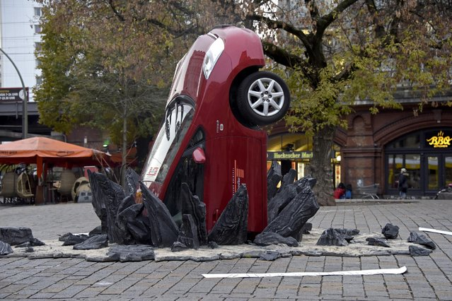 """A car """"crashed"""" into the ground at Hackescher Markt in Berlin, Germany on November 15, 2016, ahead of the launch of Jeremy Clarkson, Richard Hammond and James May's new show, """"The Grand Tour"""", on Amazon Prime Video, on Friday. (Photo by Clemens Bilan/Getty Images for Amazon Prime Video)"""