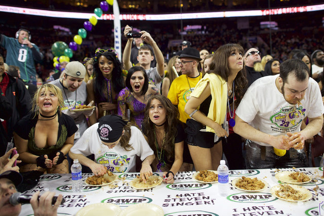 """Defending champion Molly Schuyler (2nd L) and Patrick """"Deep Dish"""" Bertoletti (R) compete in the 23rd annual Wing Bowl at the Wells Fargo Center in Philadelphia, Pennsylvania January 30, 2015. Professional competitive eater from Chicago Patrick """"Deep Dish"""" Bertoletti downed 444 chicken wings in 30 minutes at the 23rd annual Wing Bowl in Philadelphia, narrowly edging out his nearest rival and shattering the record of 363 wings set a year earlier. (Photo by Mark Makela/Reuters)"""