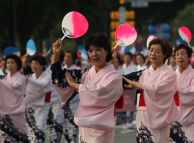 Women dress traditional in costume perform folk dance during the annual Himeji Castle Festival on August 3, 2013 in Himeji, Japan. The parade of Castle Queens is part of the traditional matsuri festival around the UNESCO world heritage Himeji Castle. (Photo by Buddhika Weerasinghe/Getty Images)