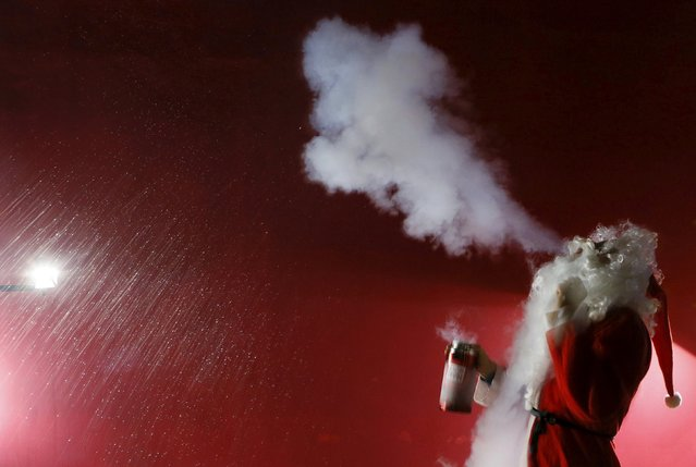 """Ivan Timofeenko, co-founder of """"Newton Park"""", a private interactive museum of science, dressed as Santa Claus, exhales a cloud of liquid nitrogen, bearing the temperature of about minus 196 degrees Celsius (minus 320.8 degrees Fahrenheit), during the """"Arctic"""" scientific show for school children at the """"Square of Peace"""" museum centre in the Siberian city of Krasnoyarsk, Russia, December 24, 2015. (Photo by Ilya Naymushin/Reuters)"""