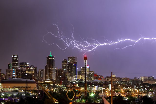A huge blast of purple-tinged lightning streaks across a row of skyscrapers in Denver, Colorado. (Photo by Greg Thow/Barcroft Media)