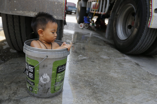 A boy bathes in a bucket next to his father's rice truck outside a rice mill in the central province of Chainat , Thailand December 16, 2015. (Photo by Jorge Silva/Reuters)
