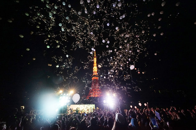 Peoples release balloons to celebrate the New Year with Tokyo Tower in the background  in Tokyo, early Friday, January 1, 2016. Japan celebrated the start of 2016, the Year of the Monkey in the Japanese Zodiac. (Photo by Eugene Hoshiko/AP Photo)
