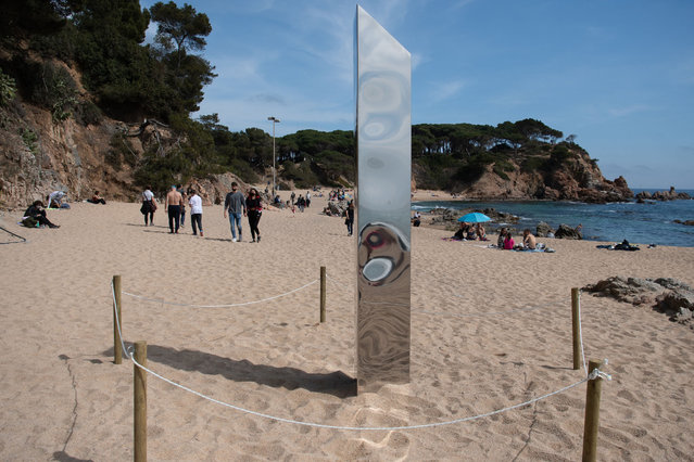 People walk on March 31, 2020 by a metal monolith that has popped up on Sa Conca beach in Castell-Platja D'Aro, near Girona, the latest in a string of similar objects that have recently appeared around the world since a first similar column appeared in a desert of Utah, United States in November 2020. (Photo by Josep Lago/AFP Photo)