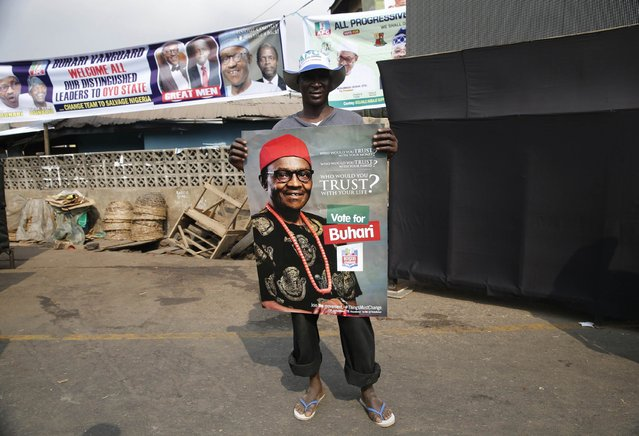 Abubakar Kadakinguda, 30, an ethnic Hausa Muslim man from the north, holds a poster campaigning for Nigeria's former military ruler and presidential candidate for All Progressives Congress (APC) Muhammadu Buhari in Ibadan, southwest Nigeria January 29, 2015.  Kadakinguda believes the political challenges in Nigeria, including security issues will be fixed if Buhari becomes the next head of government in the forthcoming elections. (Photo by Akintunde Akinleye/Reuters)