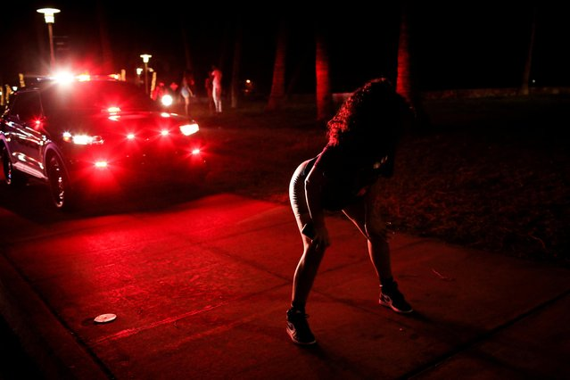 A woman dance in front of a patrol vehicle as police officers ask revelers to leave during an 8pm curfew imposed by local authorities on spring break festivities, amid the coronavirus disease (COVID-19) pandemic, in Miami Beach, Florida, U.S., March 26, 2021. (Photo by Marco Bello/Reuters)
