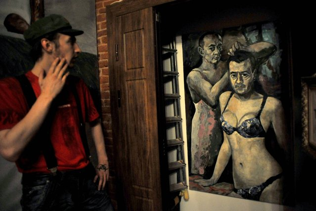 """A visitor looks at an artwork representing Russia's President Vladimir Putin and Russian Prime Minister Dmitry Medvedev by Russian artist Konstantin Altunin during the """"Leaders"""" exhibition in the cental St. Petersburg on August 21, 2013. (Photo by Olga Maltseva/AFP Photo)"""