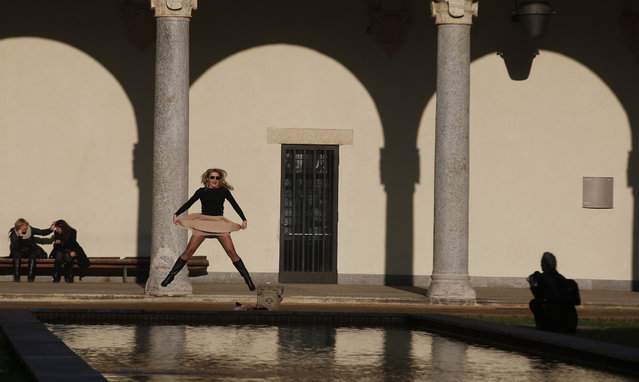 A tourist jumps as she poses for a picture at the Sforzesco Castle in Milan, Italy, Wednesday, February 11, 2015. (Photo by Luca Bruno/AP Photo)