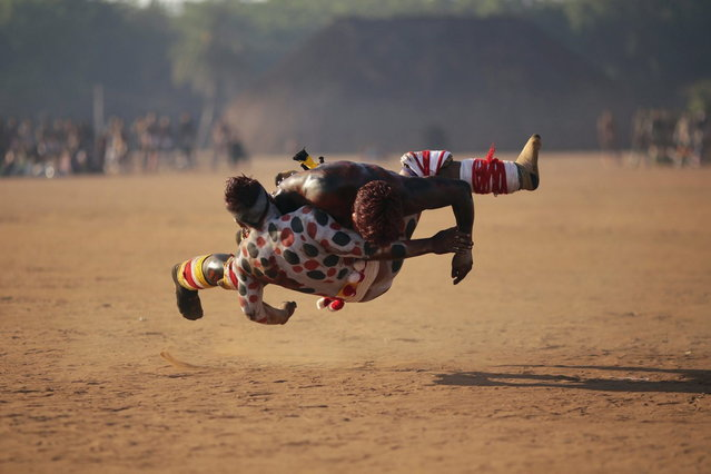 """Waura Indians wrestle during this year's """"quarup"""", a ritual held over several days to honour in death a person of great importance to them, in Xingu National Park, Mato Grosso State, August 25, 2013. This year the Waura tribe honoured their late cacique (chief) Atamai, who died in 2012, for his work creating the Xingu Park and his important contribution in facilitating communication between white Brazilians and Indians. (Photo by Ueslei Marcelino/Reuters)"""