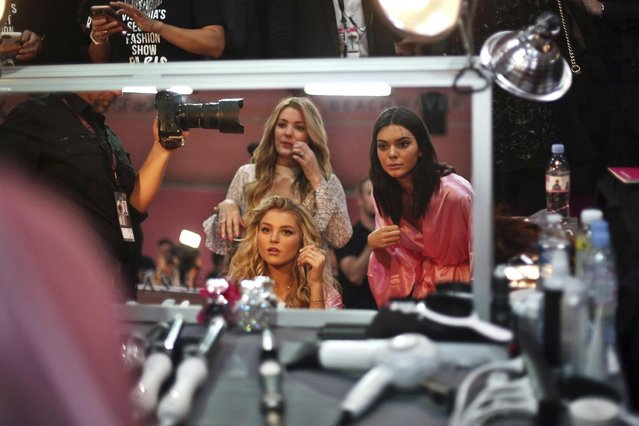 Model Kendall Jenner, right, and Martha Hunt, seated, adjust their hair before the Victoria's Secret fashion show in Paris, France, Wednesday, November 30, 2016. (Photo by Thibault Camus/AP Photo)