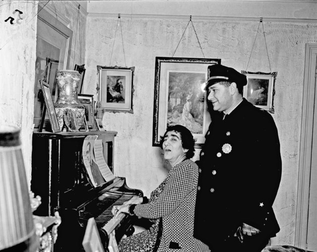 Madame Bey sits down at a piano and sings a song for her son, Rustem Bey, chief of police of Chatham Township, N.J., January 10, 1938. As stern as she is in matters of fight training discipline, Madame Bey has a softer side to her nature. She once was a concert singer, and still loves to run through her old repertoire. Rustem listens fondly to his mother's voice. (Photo by John Lindsay/AP Photo)