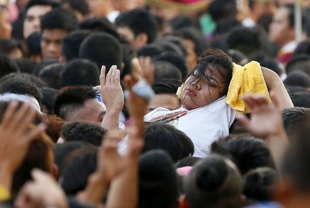 A female Catholic devotee is carried away from others for treatment during a raucous procession of the image of the Black Nazarene in celebration of its feast day in Manila, Philippines, Saturday, January 9, 2016. (Photo by Bullit Marquez/AP Photo)