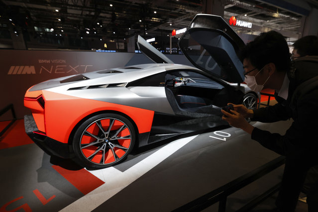 A visitor looks at the BMW Vision Next concept car displayed during the Shanghai Auto Show in Shanghai on Monday, April 19, 2021. Automakers are looking to China, their biggest market by sales volume and the first major economy to rebound from the pandemic, to revive sales and reverse multibillion-dollar losses. (Photo by Ng Han Guan/AP Photo)