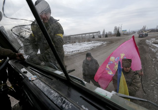 Ukrainian servicemen who fought in Debaltseve hoist flags to their vehicle before leaving for home, near Artemivsk February 19, 2015. (Photo by Gleb Garanich/Reuters)