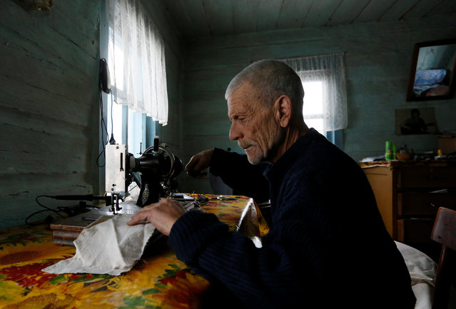Mikhail Baburin, 66, uses a sewing machine at his house in the remote Siberian village of Mikhailovka, Krasnoyarsk region, Russia, December 5, 2016. (Photo by Ilya Naymushin/Reuters)
