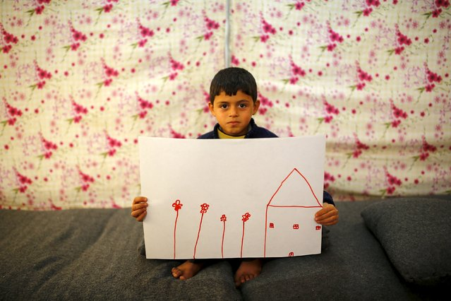 Syrian refugee boy Ali Addahar, 9, shows his drawing of his home in Syria as he sits in his tent in Midyat refugee camp in Mardin province, Turkey, December 14, 2015. (Photo by Umit Bektas/Reuters)