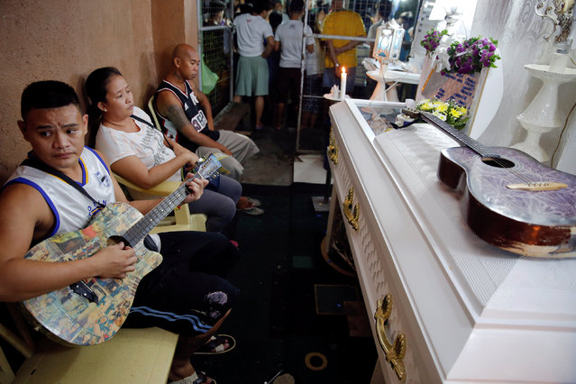 Friends and relatives of Florjohn Cruz, who was killed in a police drugs buy-bust operation, gather around his coffin during his wake in Manila, Philippines late October 20, 2016. (Photo by Damir Sagolj/Reuters)
