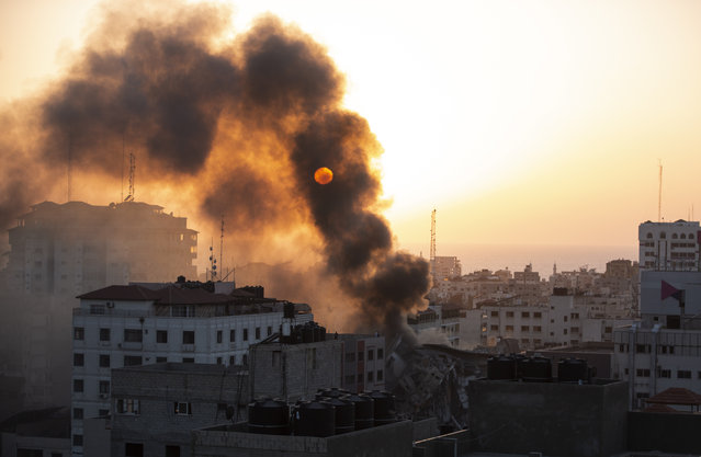 Smoke is seen from a collapsed building after it was hit by Israeli airstrikes on Gaza City, Wednesday, May 12, 2021. The Israeli airstrike was the latest in a series of assaults on targets in the Gaza Strip after a long dispute between Israel and Hamas erupted into an exchange of rocket attacks from Gaza and Israeli retaliation. (Photo by Khalil Hamra/AP Photo)