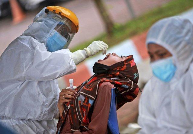 A medical worker collects nasal swab samples from a woman during a mass test for coronavirus at North Sumatra University (USU) Hospital in Medan, North Sumatra, Indonesia, Wednesday, June 2, 2021. (Photo by Binsar Bakkara/AP Photo)