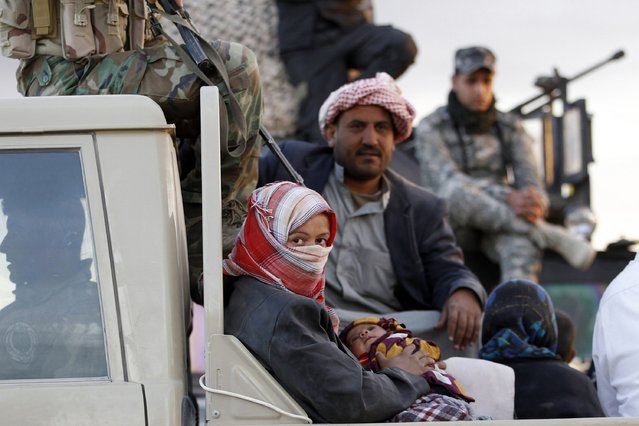 A woman with her child sits in a military vehicle as she returns home at the town of Tal Ksaiba, near the town of al-Alam March 7, 2015. (Photo by Thaier Al-Sudani/Reuters)