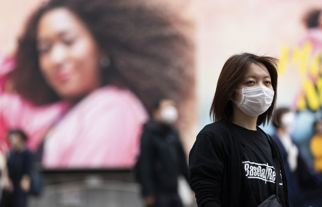 A woman wearing a face mask waits for the traffic lights to change at the famed Shibuya crossing in Tokyo on Thursday, May 20, 2021. (Photo by Hiro Komae/AP Photo)