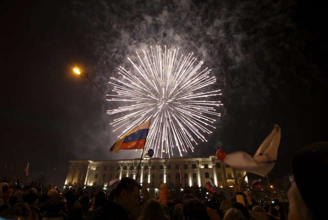 In this Friday, March 21, 2014 file photo people watch fireworks at the central Lenin square in Simferopol, Crimea, as Russian President Vladimir Putin completed the annexation of Crimea on Friday, signing a law making the Black Sea peninsula part of Russia. (Photo by Ivan Sekretarev/AP Photo)
