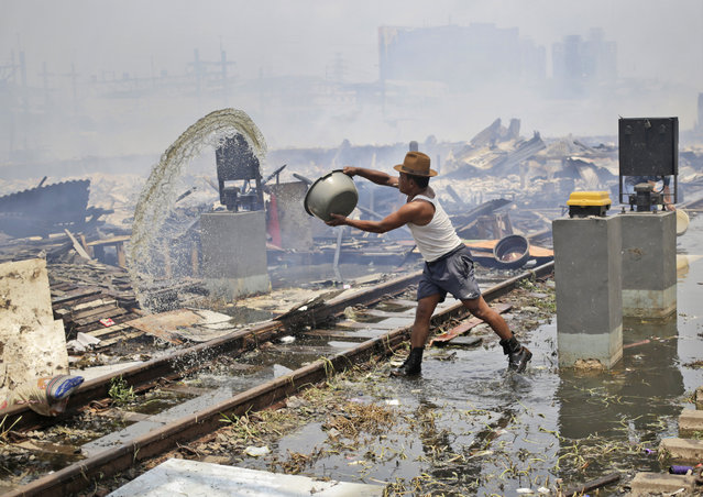 A man throws a bucket of water to cool down the rubble of houses burned down by a fire that razed through a slum in Jakarta, Indonesia, Tuesday, January 26, 2016. (Photo by Dita Alangkara/AP Photo)