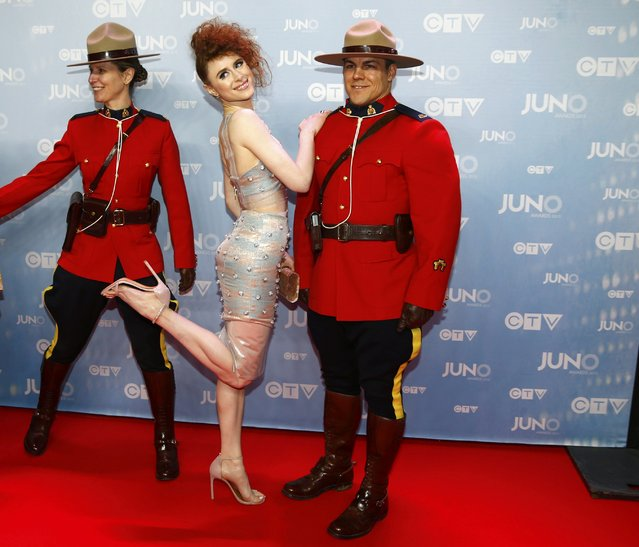 Calgary-based singer Kiesa Rae Ellestad, better known as Kiesza, poses with Royal Canadian Mounted Police officers as she arrives at the 2015 Juno Awards in Hamilton, Ontario, March 15, 2015. (Photo by Mark Blinch/Reuters)