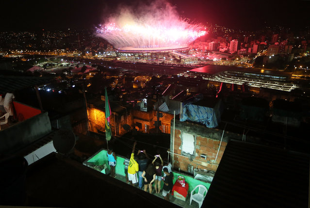 """Fireworks explode over Maracana stadium with the Mangueira """"favela"""" community in the foreground during opening ceremonies for the Rio 2016 Olympic Games on August 5, 2016 in Rio de Janeiro, Brazil. The Rio 2016 Olympic Games commenced tonight at the iconic stadium. (Photo by Mario Tama/Getty Images)"""