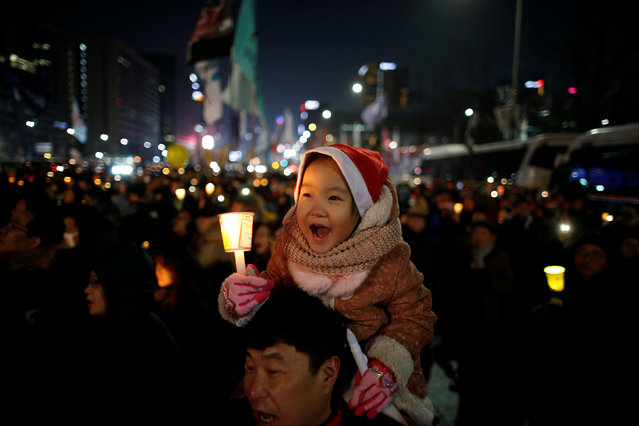 A child sitting on his father's shoulder holds a candlelight during a protest demanding South Korean President Park Geun-hye's resignation in Seoul, South Korea, December 24, 2016. (Photo by Kim Hong-Ji/Reuters)
