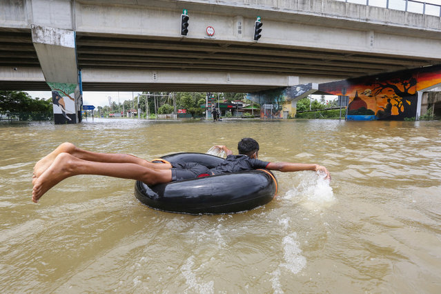 A Sri Lankan child uses an inflatable tube to wade through floodwaters after heavy rains in Biyagama suburb of Colombo, Sri Lanka, 06 June 2021. Many parts of the island have been inundated due to heavy monsoon rains. According to the Sri Lanka Disaster Management Center, at least 14 people have been killed so far and more than 245,212 people affected across the country. (Photo by Chamila Karunarathne/EPA/EFE)