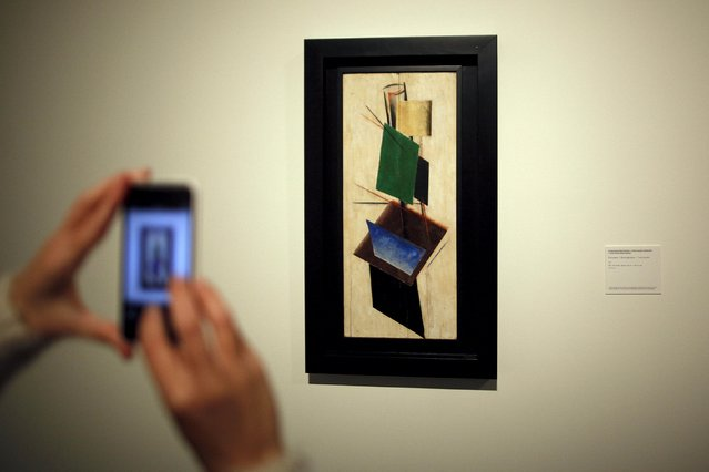 """A woman takes pictures of """"Construction"""" by Russian-born artist Alexander Rodchenko during an international press tour of the Malaga branch of the State Museum of Russian Art of St Petersburg, a day before its inauguration in Malaga, southern Spain March 24, 2015. (Photo by Jon Nazca/Reuters)"""
