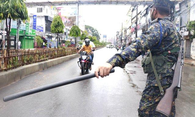 A policeman stops commuters in Rajshahi, 254 kilometers (158 miles) north of the capital, Dhaka, Bangladesh, June 16, 2021. (Photo by Kabir Tuhin/AP Photo)