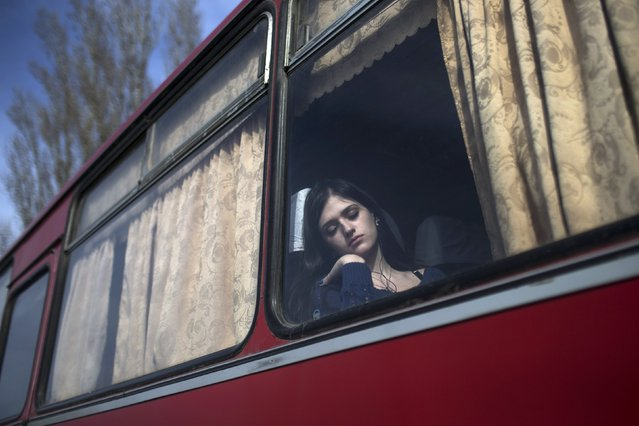 A woman takes a nap inside a bus while waiting to cross the Uspenka border crossing between Ukraine and Russia, southeast from Donetsk March 15, 2015. (Photo by Marko Djurica/Reuters)