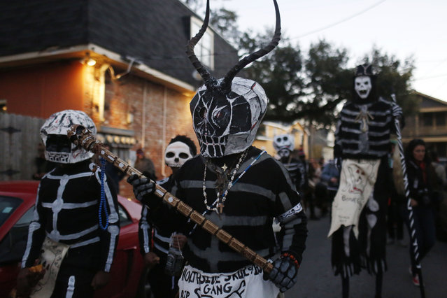 The North Side Skull & Bone Gang parade down the streets during the wake up call for Mardi Gras, Tuesday, February 9, 2016, in New Orleans. Their costumes are intended to represent the dead and they bring a serious message, reminding people of their mortality and the need to live a productive and good life. (Photo by Brynn Anderson/AP Photo)