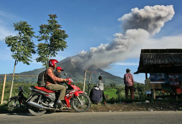 Villagers watch Mount Sinabung spewing volcanic ash into in Tiga Pancur, North Sumatra, Indonesia, Monday, November 25, 2013. Powerful bursts of hot ash and gravel erupted from the rumbling volcano in western Indonesia Monday, a day after authorities had raised the volcano's alert status to the highest level. (Photo by Binsar Bakkara/AP Photo)