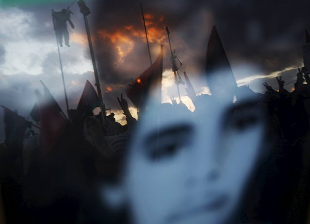 Anti-Gaddafi protesters hanging effigies of Libyan leader Muammar Gaddafi are reflected in a photo of a youth who was killed in clashes in Benghazi March 6, 2011. (Photo by Suhaib Salem/Reuters)