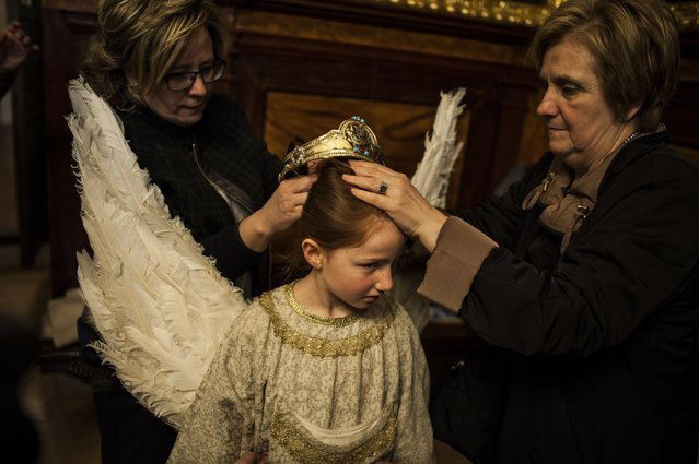 """Relatives of eight-year-old Alba Oroz, center, adjust her crown  during the Easter Sunday ceremony """"Descent of the Angel"""", during Holy Week in the small town of Tudela, northern Spain, Sunday, April 5, 2015. (Photo by Alvaro Barrientos/AP Photo)"""