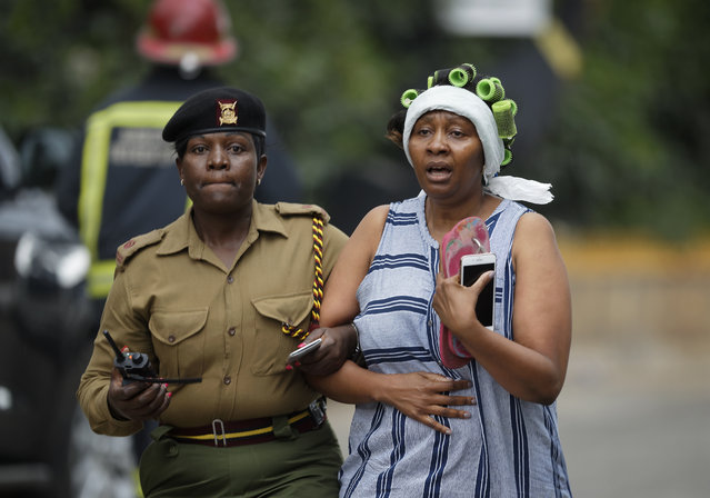 A civilian flees the scene assisted by a member of security forces, at a hotel complex in Nairobi, Kenya Tuesday, January 15, 2019. Terrorists attacked an upscale hotel complex in Kenya's capital Tuesday, sending people fleeing in panic as explosions and heavy gunfire reverberated through the neighborhood. (Photo by Ben Curtis/AP Photo)