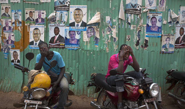 Dejected opposition supporters who work as motorbike taxi drivers hold their heads in their hands shortly after the election result was announced, in downtown Kampala, Uganda Saturday, February 20, 2016. Long-time Ugandan leader Yoweri Museveni was on Saturday declared the winner of the country's disputed presidential election, but the main opposition party rejected the results as fraudulent and called for an independent audit of the count. (Photo by Ben Curtis/AP Photo)