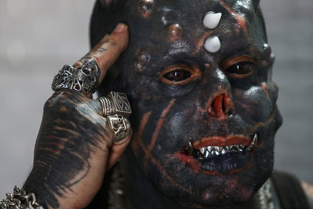 Brazilian tattoo artist Michel Praddo, also known as Diabao or Human Satan, talks about his body modifications in his studio in Praia Grande, Brazil on August 18, 2021. (Photo by Carla Carniel/Reuters)