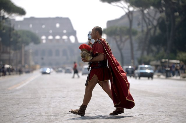 A man dressed as a ancient Roman centurion walks by the Colosseum in the center of Rome on April 15, 2015. (Photo by Filippo Monteforte/AFP Photo)