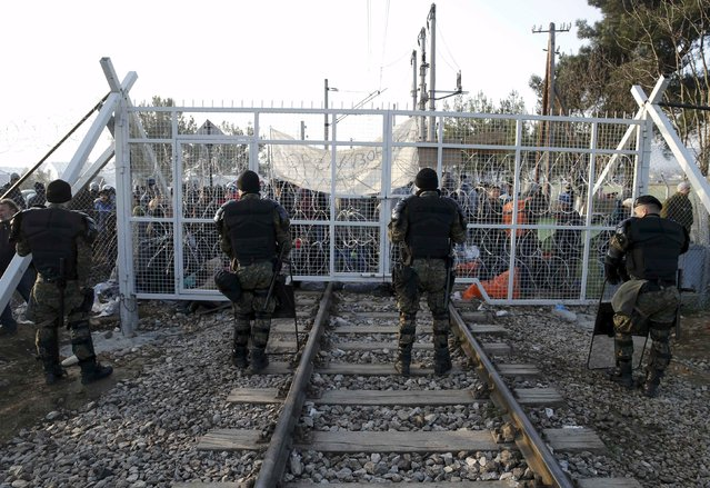 Macedonian policemen stand in front of a gate over rail tracks as migrants wait behind at the Greek-Macedonian border, after additional passage restrictions imposed by Macedonian authorities left hundreds of them stranded near the village of Idomeni, Greece, February 23, 2016. The picture was taken from the Macedonian side of the border. (Photo by Marko Djurica/Reuters)