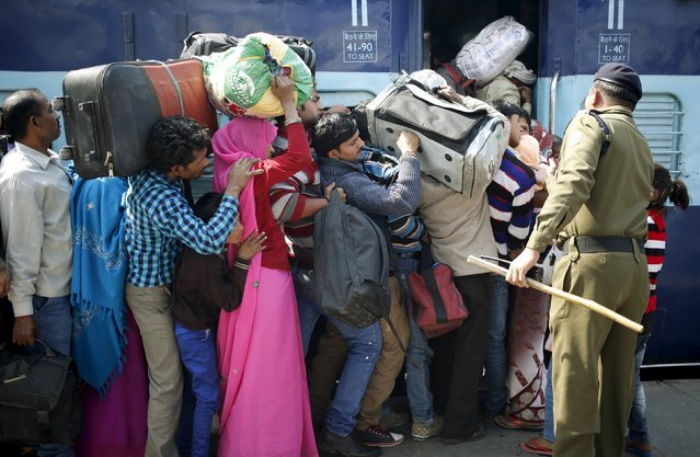 A policeman keeps order as people board a passenger train at a railway station in New Delhi, India, February 25, 2016. (Photo by Anindito Mukherjee/Reuters)