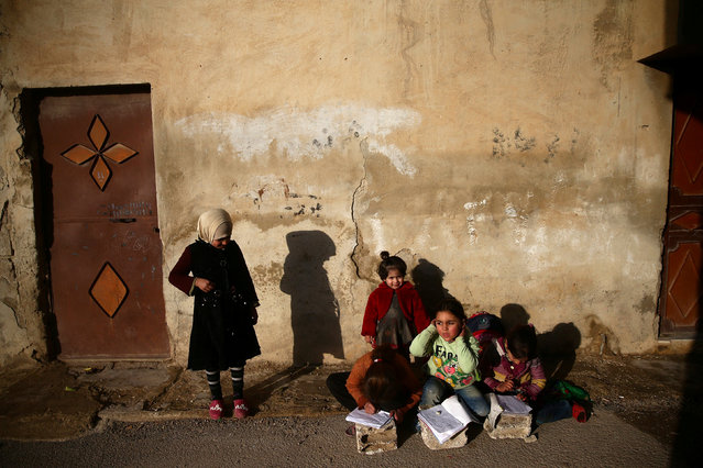 Girls write on notebooks in the rebel held besieged Douma neighbourhood of Damascus, Syria January 17, 2017. (Photo by Bassam Khabieh/Reuters)