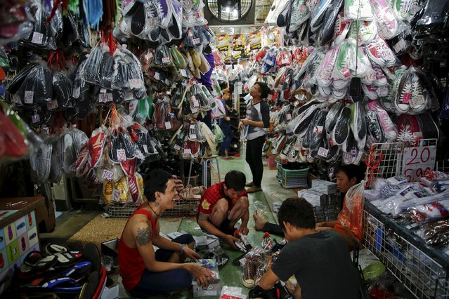 Boys pack shoes for sale at a market in central Bangkok in this August 1, 2014 file photo. (Photo by Damir Sagolj/Reuters)