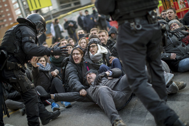 Catalan police officers remove demonstrators blocking a road leading to Barcelona city, during a general strike in Catalonia, Spain, Thursday, February 21, 2019. Strikers advocating for Catalonia's secession from Spain are blocking major highways, train lines and roads across the northeastern region. (Photo by Emilio Morenatti/AP Photo)